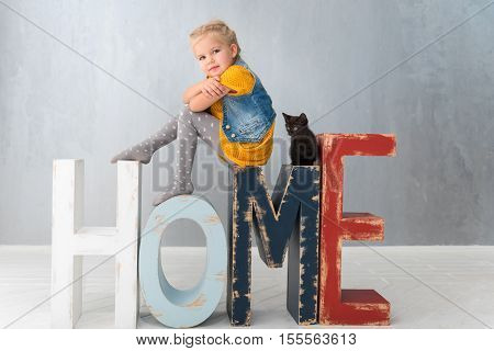 Letters HOME. Nice thoughtful pretty girl sitting near the kitten and crossing her arms while thinking about something