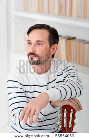 Always with my guitar. Handsome good looking brunette man sitting and looking somewhere while resting his hands on the guitar