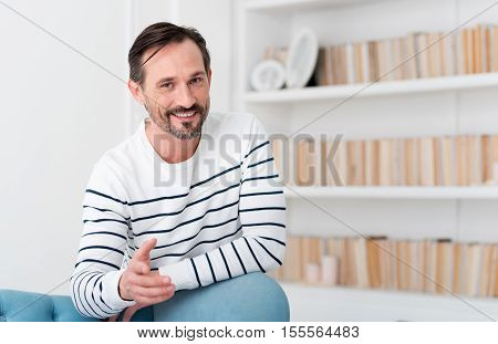 Friendly person. Good looking handsome delighted man stretching out his hand and looking at you while leaning on the sofa