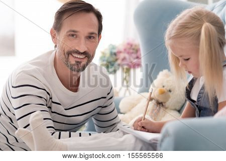 Home lesson. Nice handsome joyful man looking at you and smiling while helping his daughter with studying