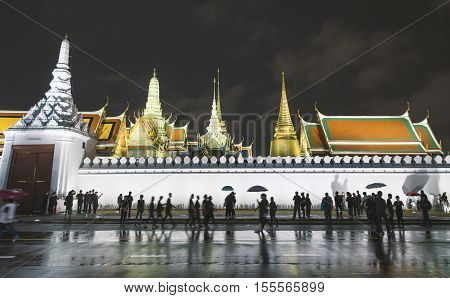 Bangkok Thailand - October 26 2016: Grand palace or Wat Prakaew at night with black dress crowd to mourn the pass away King Bhumibol Adulyadej.