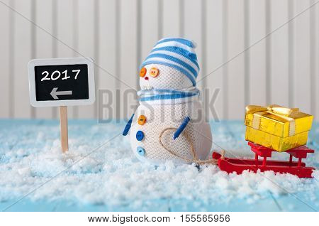 New Year 2017 is coming concept. Snowman with red sled stand near written on direction sign 2017