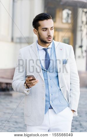 Portrait of stylish handsome young man with bristle standing outdoors