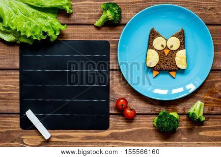 children's menu place for text with owl shaped sandwich on blue plate top view at wooden background