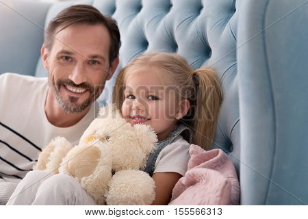 Sincere happiness. Happy joyful sweet girl sitting with her father on the couch and smiling while holding a teddy bear