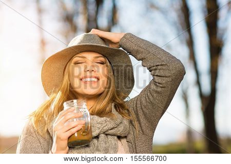 Closeup of gorgeous happy young blonde woman with coffee in park in autumn. Modern beautiful teenage girl in gray outfit and floppy hat smiling, enjoying sunny fall day outside.