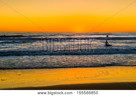 Surfers on the waves. Sunset over the ocean in San Diego. Coast southern California.