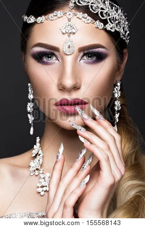 Beautiful girl in the image of the Arab bride with expensive jewelry, oriental make-up and bridal manicure. The beauty of the face. Photos shot in the studio.
