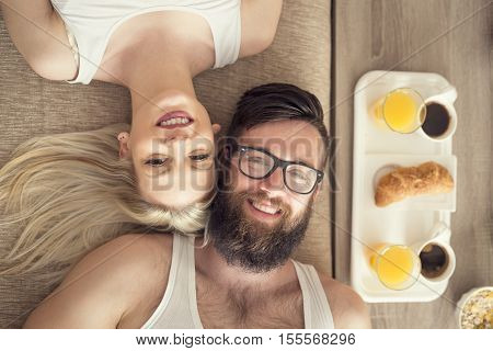 Top view of a young couple in love lying on a couch getting up in the morning and having breakfast in bed