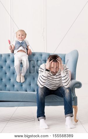 Naughty child. Sad handsome thoughtful father sitting on the couch and holding his head while thinking what to do with his daughter