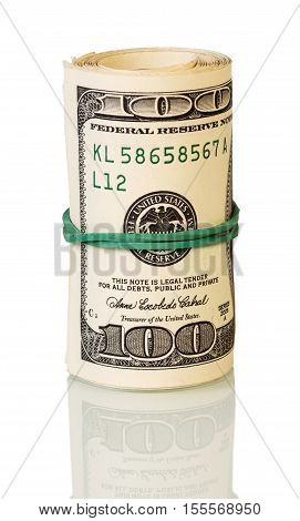 Dollars in roll fastened by rubber band isolated on white background.