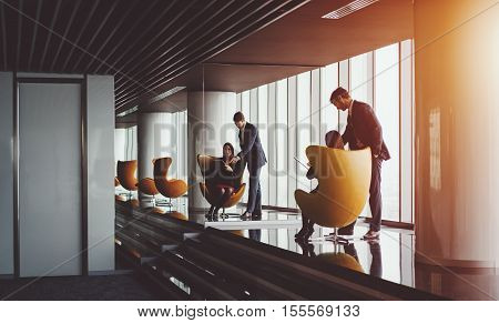 Smiling businesswoman in red dress and jacket on yellow armchair showing information on screen of her digital tablet to her boss in formal suit luxury office interior with a lot of reflections