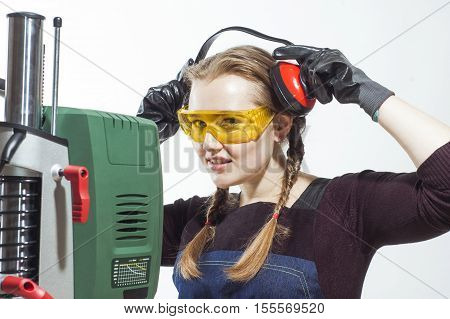 Female construction worker wearing protective headphones and level safety glasses