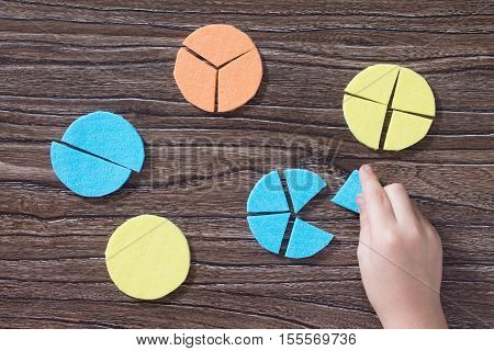 Hand Of A Child Holds Missing Part Of The Puzzle In The Study Of Mathematical Fraction On A Wooden T