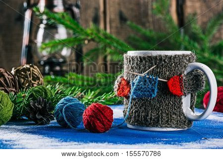 Mug with woolen warmer holding toothpicks as knitting needles on the table with christmas decorations