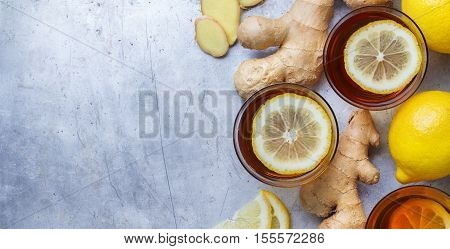Ginger tea in a glass with ingredients. Hot drink for cold flu winter autumn on a rustic metal table. Selective focus, copy space background, top view flat lay