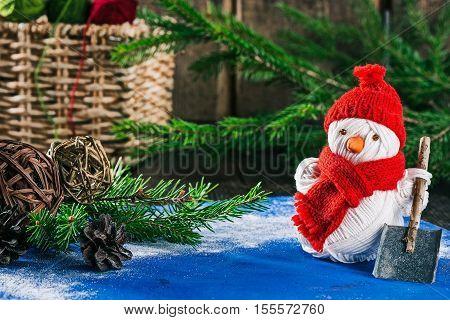 Handmade yarn snowman holding shovel on the background of christmas decorations
