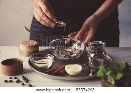 Woman making coffee body scrub on wooden table