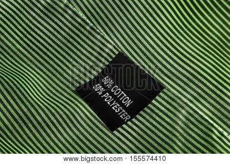 Fabric composition label on striped green cloth as a background