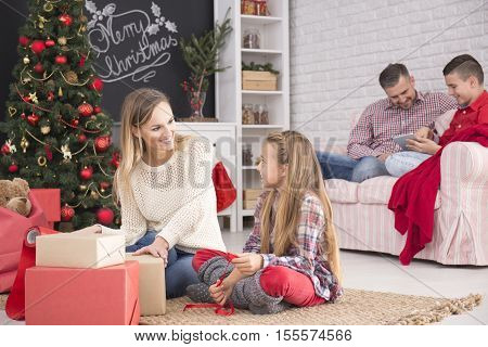 Mother And Daughter Unwrapping Gifts