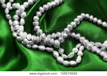 Strings of pearl on green satin as a background