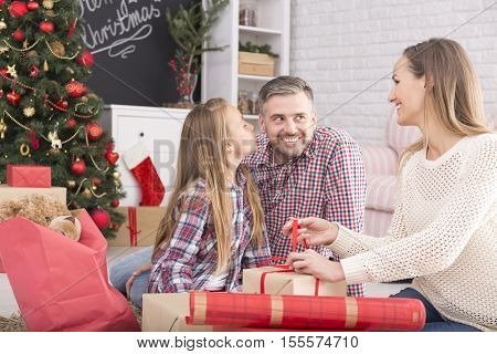 Woman wrapping christmas gift box daughter kissing her father's chick