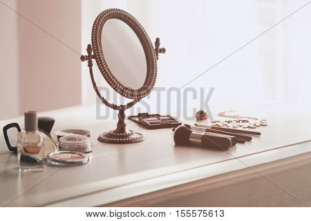 Vintage mirror and cosmetics on white table against light background