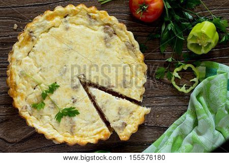 A Classic Quiche Lorraine Pie With Potatoes, Meat And Cheese In A Baking Dish On A Table In A Rustic