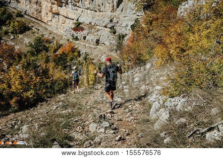 couple hikers with walking poles travel mountains in autumn day