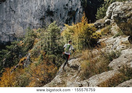 male runner with walking poles and a backpack runs along cliff steep