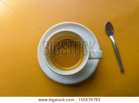 Cup of hot espresso coffee on yellow Leather table - Top view One cup espresso coffee in a relax time.