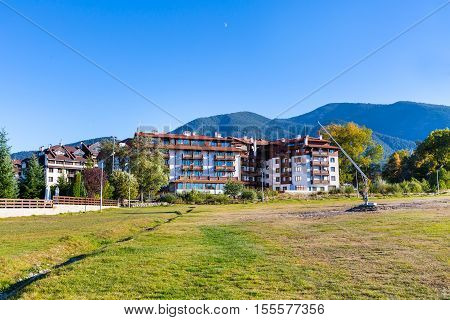 Bansko, Bulgaria - October 8, 2016: Autumn trees, mountains landscape and hotel houses in Bansko, Bulgaria