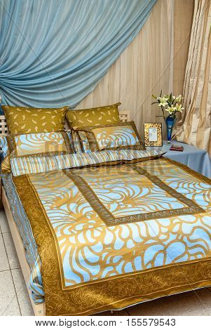 Bed In The Bedroom With The Blue Gold Linens