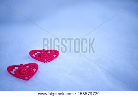 Wooden figures of red hearts on a background of snow tonight