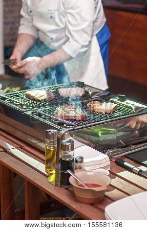 Chef Man In Uniform Frying A Meat Beefsteak Slice On Grill