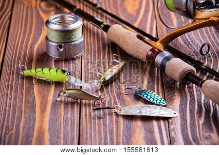Fishing gear - fishing spinning fishing line hooks and lures on wooden background