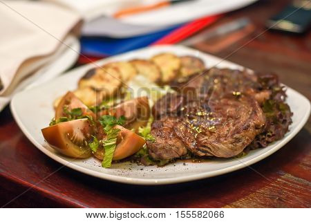 Steak With Vegetables On A White Plate