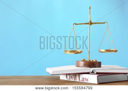 Justice scales and books on wooden table and blue background