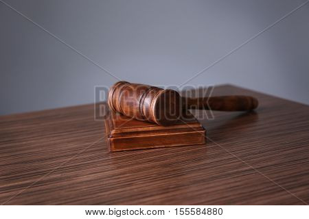 Judges gavel on wooden table and grey background