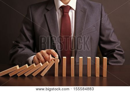 Businessman hand trying to stop toppling dominoes on table