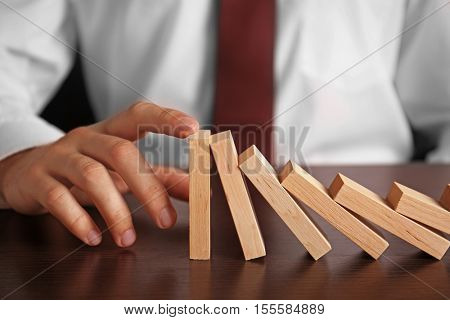 Businessman hand trying to stop toppling dominoes on table poster