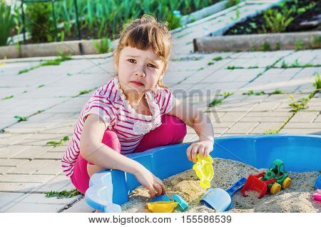 a small sad girl playing in a sandbox in the yard on a summer day