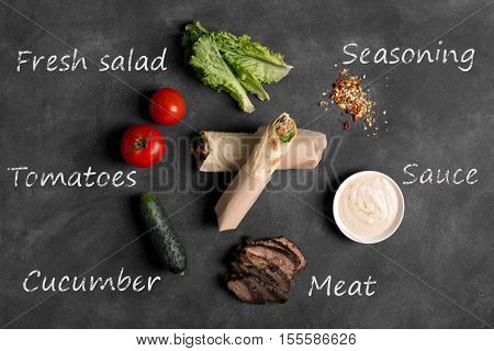 Doner kebab - fried beef meat with vegetables in tortilla on the black chalkboard with ingredients inscriptions
