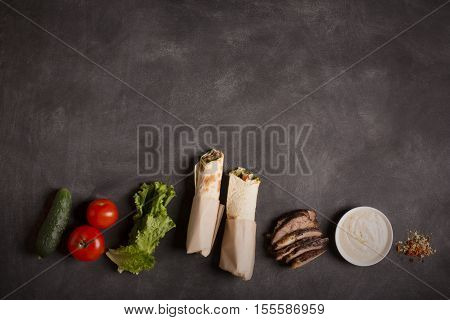 Doner kebab - fried beef meat with vegetables in tortilla on the black chalkboard. Copy space