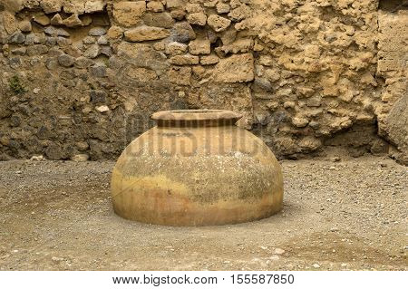 Ancient amphorae on the backdrop of a stone wall in ruins of Pompeii.