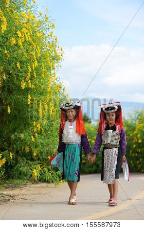 Two young asian Lahu tribe girls in custom dress walk with smile and happy.