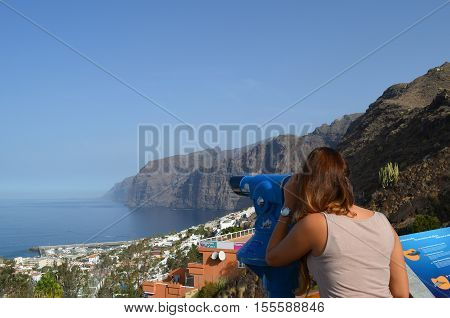 young girl looks through a telescope to see the cliffs and ocean