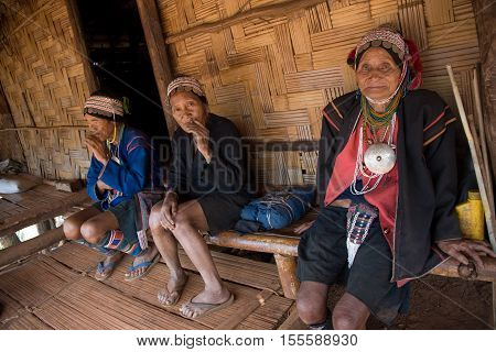 Mae Salong, Thailand - January 28, 2008 :  In the province of Mae Salong, north of Thailand.  Three old women from the Akha ethnic group rests in the shadow of her bamboo house