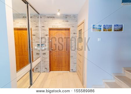 Entrance hall in modern apartment with mirror wardrobe with sliding doors
