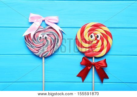 Sweet Lollipop With Googly Eyes On Blue Wooden Table